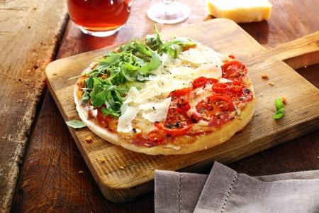 bandera italiana: Colorido pizza italiana con los colores nacionales cubierto con hojas verdes frescas del cohete, virutas de queso blanco y tomates rojos en tres rayas de pie sobre una tabla de madera en una vieja mesa rústica