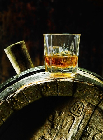 A glass of whiskey with ice on an old oak barrel using dramatic lighting. photo