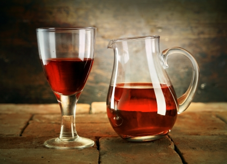 barrel tile: A glass of red wine with a jug of wine on a rustic table.