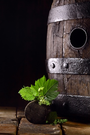Old oak wine barrel with fresh young vine leaves balanced on the bung off a grapevine standing on old bricks against a dark background with copyspace photo
