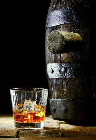 Un vaso de whisky con hielo y una barrica de roble photo