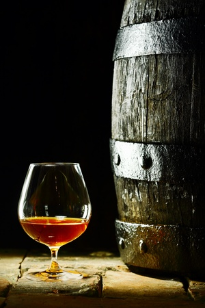 Cognac snifter with glowing golden cognac standing on old flagstones or tiles alongside an old oak barrel in a dark cellar, conceptual of aged matured cognac with copyspace photo