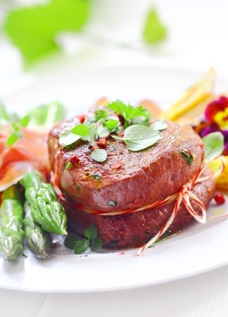 thinly: Succulent tender fillet steak medallion tied with string and served with fresh green asparagus spears wrapped in thinly sliced ham or bacon Stock Photo