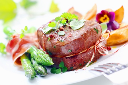 thinly: Thick juicy steak with fresh green asparagus spears wrapped in thinly sliced ham or bacon served garnished with herbs and crisp golden roast potatoes Stock Photo