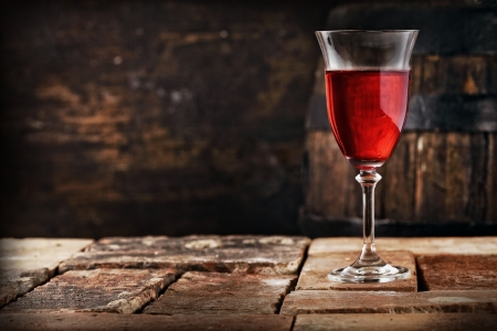 A glass of red wine on an old rustic table, shallow depth of field.