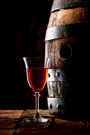 A glass of red wine next to an old oak cask with its stopper out.