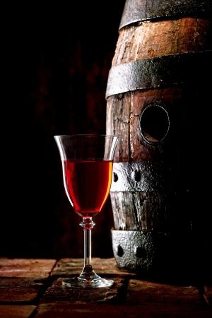 Un bicchiere di vino rosso accanto a una vecchia botte di rovere con il suo tappo fuori. Archivio Fotografico - 20281120
