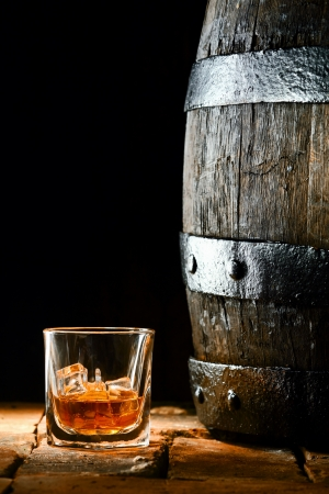 wood barrel: Glass of golden matured premium brandy or whiskey on the rocks alongside an old oak barrel standing upright on old bricks with a dark background Stock Photo