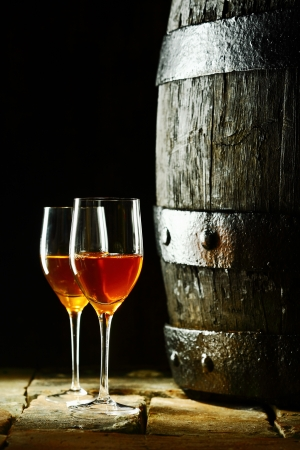 Old oak wine barrel with two glasses of sherry against a dark background reminiscent of a cellar in a winery