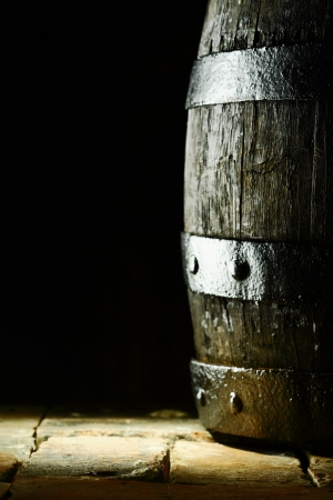 Old oak barrel standing upright on flagstones or old bricks with a dark background and copyspace conceptual of the aging and storing of wine, brandy or beer