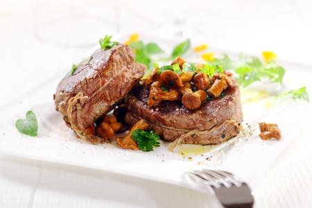 フィレ肉のステーキの厚さのジューシーなメダリオンのグルメ ディナーは野生のマッシュルームでトッピングされたひもで結んでし、白い大皿にハ