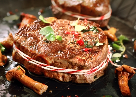 Closeup view of an appetizing grilled medallion of fillet and wild mushrooms seasoned with spice and fresh herbs