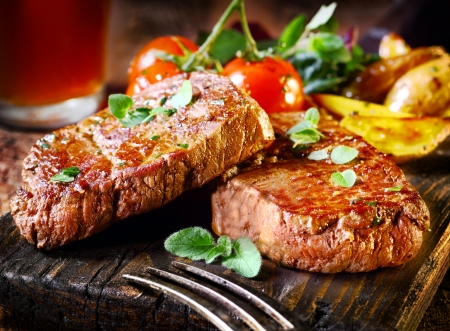 steaks: Succulent thick juicy portions of grilled fillet steak served with tomatoes and roast vegetables on an old wooden board