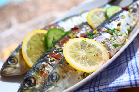 cooked fish: Close-up of three grilled sardines with lemons slices on a platter over a table outdoors Stock Photo