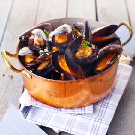 nether: Copper pot of gourmet mussels served on a napkin garnished with fresh herbs for a tasty seafood meal Stock Photo