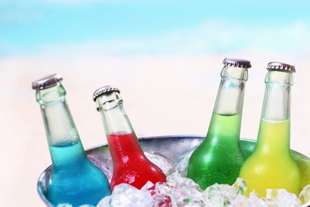 liquid summer: Colourful chilled soda drinks in unlabeled glass bottles standing in a metal container of crushed ice cubes for a summer party