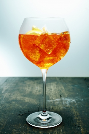 Chilled tropical aperol, rum and orange cocktail in an elegant wine glass standing on a wooden counter in a bar or club photo