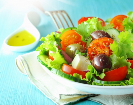 Closeup view of a plate of healthy fresh Greek feta and olive salad with crisp lettuce and tomato for a delicious Mediterranean cuisine Stock Photo