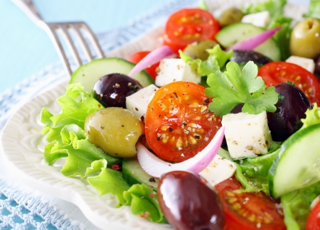 Delicious Greek salad with feta cheese, olives, tomato, cucumber and crispy lettuce garnished with chopped parsley photo