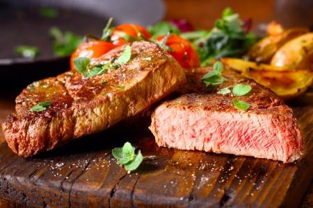 건강 한 구운 된 마른 중간 희귀 한 쇠고기 스테이크의 맛있는 부분을 잘라내어 신선한 허브와 garnished 나무 부엌 보드에 재직했습니다.