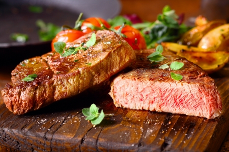 cut through: Delicious portion of healthy grilled lean medium rare beef steak cut through and served on a wooden kitchen board garnished with fresh herbs