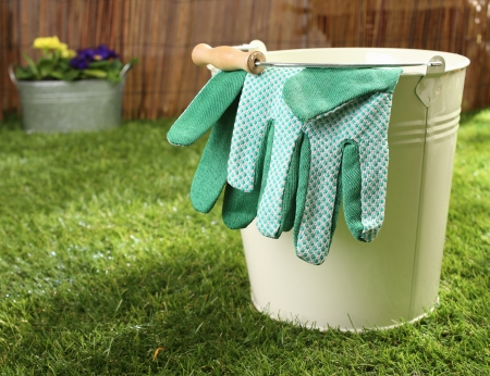 Green textile gardening gloves hanging over the rim of a metal bucket standing on a green lawn in summer sunshine, conceptual image photo