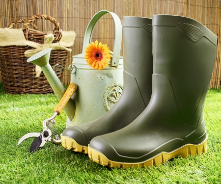 Pair of green rubber gumboots, pruning shears and a metal watering can on a neatly trimmed green lawn with a wicker basket in the background photo