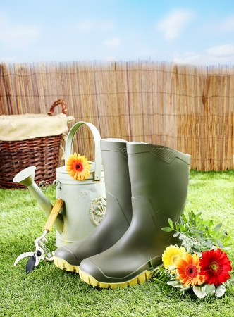 Gardener tools and equipment like rubber boots, a watering can, pruning shears and a wicker basket on a green lawn and among flowers on a bright sunny day photo