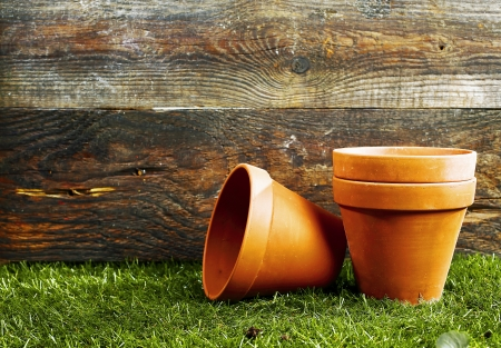 Empty earthenware terracotta flower pots on a trimmed green lawn against the wall of a wooden garden shed with copyspace photo
