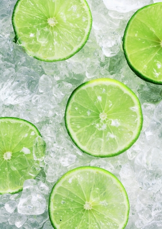 crushed by: Close-up of five fresh slices of green limes over crushed ice cubes