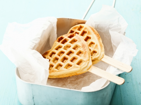 Fun crisp golden heart-shaped waffle with the traditional honeycomb pattern and a wooden stick on crumpled paper in a tin photo