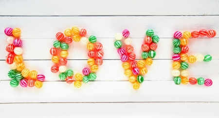 pic: The Love word written with several types of sweet candies over a white wooden board background