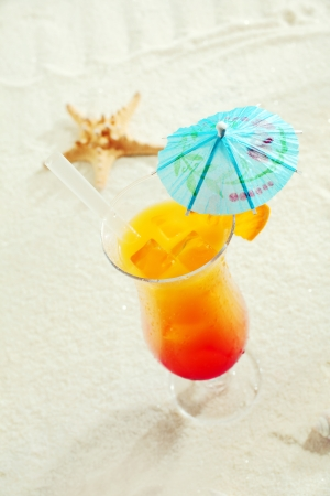 paper umbrella: Cocktail tropicale con ombrello di carta sulla sabbia