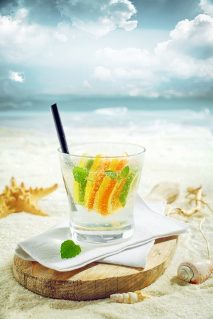 Delicious gin or vodka citrus cocktail served on a sunny tropical beach on a rustic wooden board with ocean backdrop photo