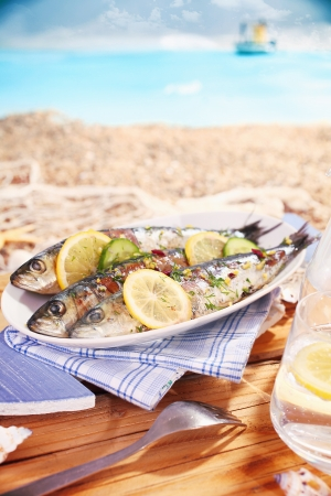 Whole garnished pan fried fish served at the beach on an oval platter garnished with lemon while enjoying a tropical summer vacation Stock Photo