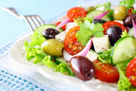 Delicious fresh mixed Greek salad with crispy lettuce, cherry tomato, onion, cucumber, olives and feta cheese served on a white plate with a silver fork photo