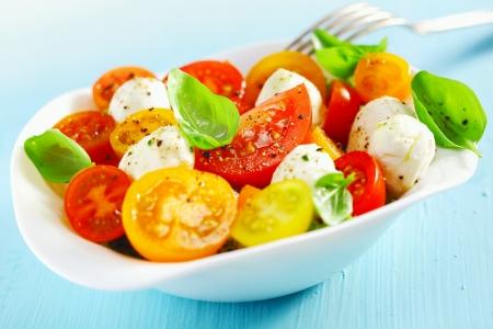 tomate cherry: Taz�n de fuente blanco de ensalada mediterr�nea fresca y saludable con queso mozzarella, tomate y hojas de albahaca y un tenedor sobre una mesa azul Foto de archivo