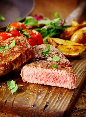 steak beef: Portion of healthy lean grilled beef steak sliced through to reveal the rare interior served on a wooden board with roast vegetables Stock Photo