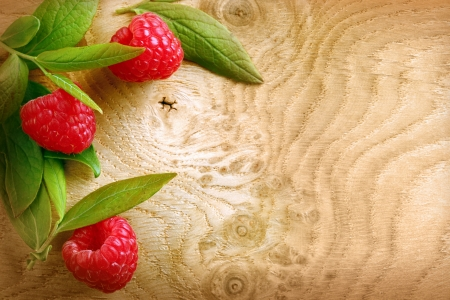 Ripe red raspberries and leaves on a patterned woodgrain texture with copyspace photo