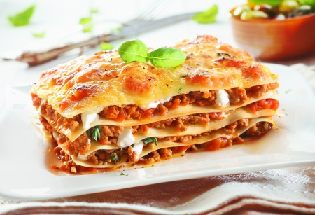 bolognese: Close-up of a traditional lasagna made with minced beef bolognese sauce topped with basil leafs served on a white plate