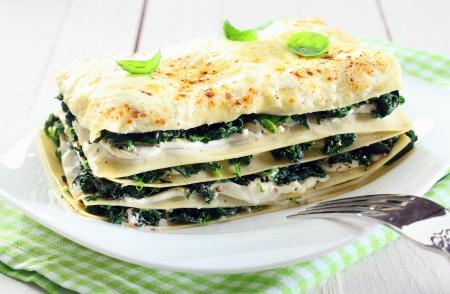 espinacas: Primer plano de un recién horneados lasaña vegetariana espinacas en un plato con un tenedor y sobre una servilleta y una vieja mesa de madera blanca
