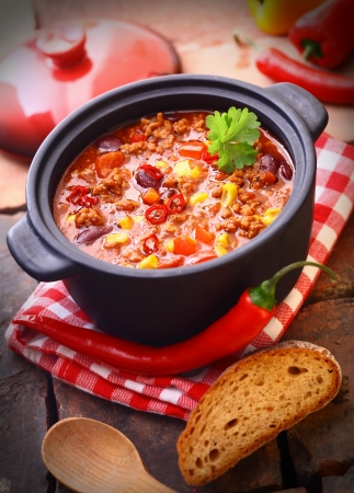 chili: Hot and spicy fresh made Mexican chili still in an iron pot, with a raw chili-pepper and a slice of bread