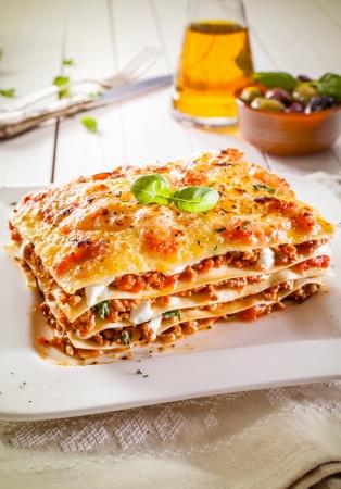 Gedeelte van de traditionele harde tarwe lasagne bolognaise saus, rundergehakt en kaas in afwisselende lagen op een witte plaat Stockfoto