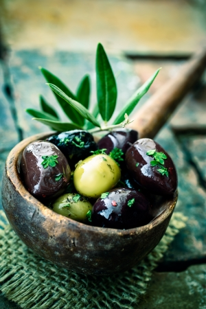 black  olive: Old wooden ladle or large spoon filled with seasoned black and green olives decorated with an olive-tree branch Stock Photo