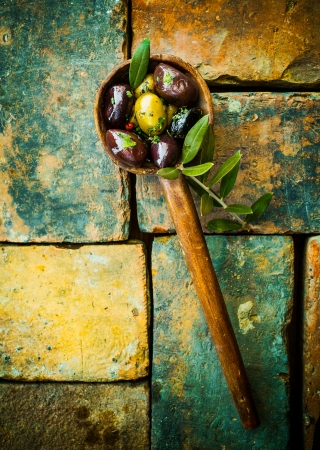 Overhead view of green and black olives in an old wooden ladle with leaves lying on grunge bricks with remnants of old paint with copyspace photo