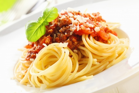 coiled: Closeup of coiled cooked Italian spaghetti topped with Bolognese sauce and garnished with fresh basil leaves