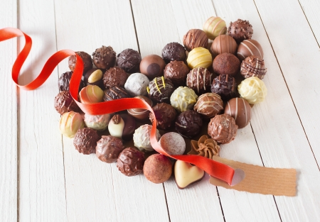 Close-up of a heart shape made with various types of chocolate truffles decorated with a blank tag for copy-space and a red curly ribbon over a white wooden table Фото со стока