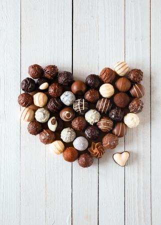 trufas de chocolate: Forma de coraz�n hecha con diversos tipos de trufas de chocolate sobre una mesa de madera blanca Foto de archivo