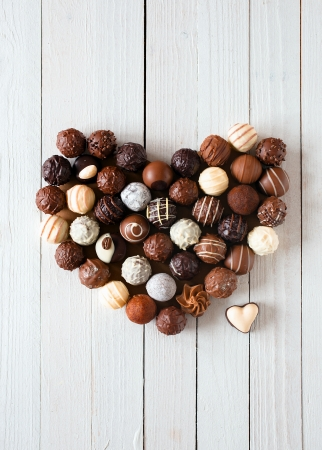 praline: Hart vorm gemaakt met verschillende soorten chocolade truffels op een witte houten tafel