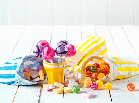 Assortment of many candy types with marshmallows and lollipops in bags and cup laid over a white wooden table